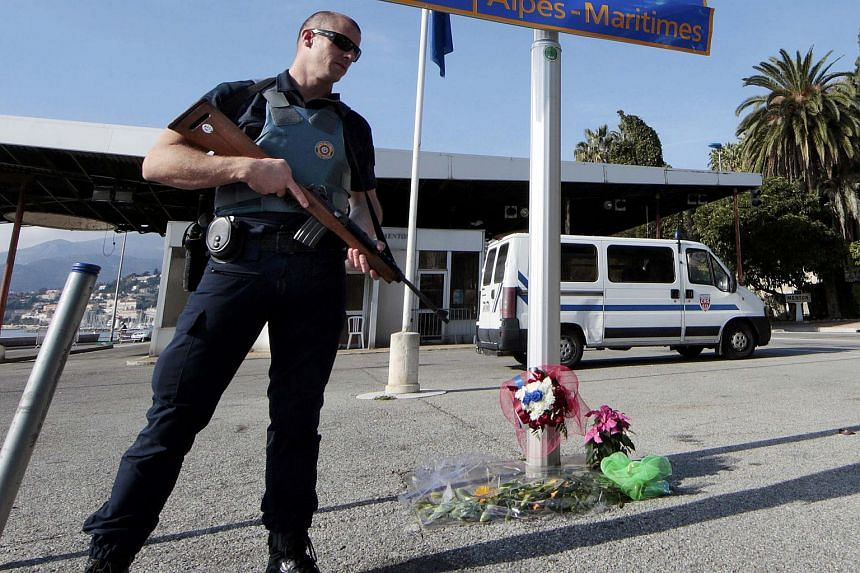 An armed French police office stands guard at the Franco-Italian border to check vehicles and identities of travellers in France.