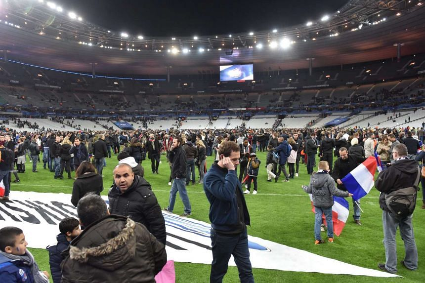 Spectators gathering on the pitch at the Stade de France in the aftermath of the Paris attacks on Nov 13, 2015.