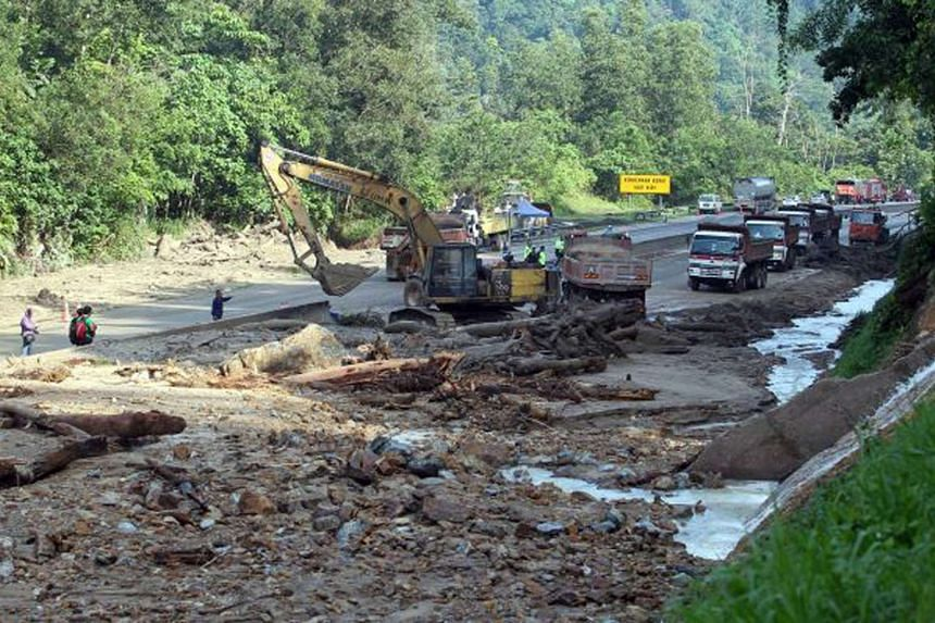 An excavator clearing mud and debris from the Kuala Lumpur-Karak Highway on Nov 12, 2015, after a landslide blocked all traffic on the route.