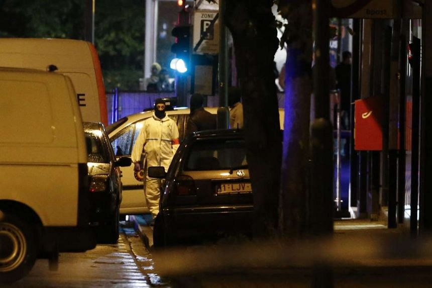 Police officers investigating in the streets of Molenbeek, Brussels.