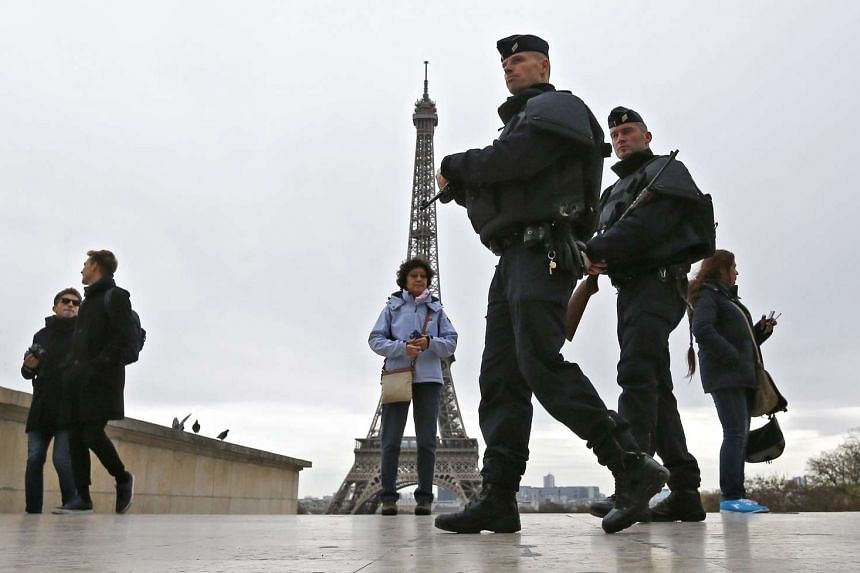 Police officers patrol next to the Eiffel tower in Paris on Nov 14, 2015.