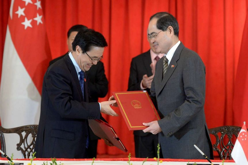 Singapore's Minister for Trade and Industry Lim Hng Kiang (right) and China's Minister of Commerce Gao Hucheng exchanging documents to officially launch negotiations to upgrade the China-Singapore free trade agreement at the Istana on Nov 7.