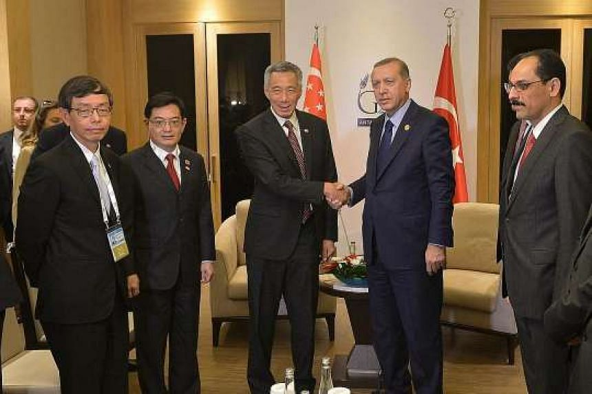 Prime Minister Lee Hsien Loong meeting Turkish President Recep Tayyip Erdogan in Antalya yesterday. With them are (from left) Civil Service head Peter Ong, Finance Minister Heng Swee Keat and Turkey's presidential spokesman Ibrahim Kalin (right).