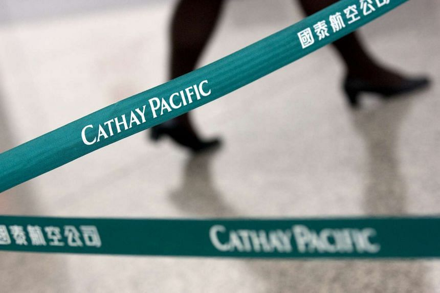 A woman walking past a Cathay Pacific Airways check-in counter at Chek Lap Kok International Airport in Hong Kong.