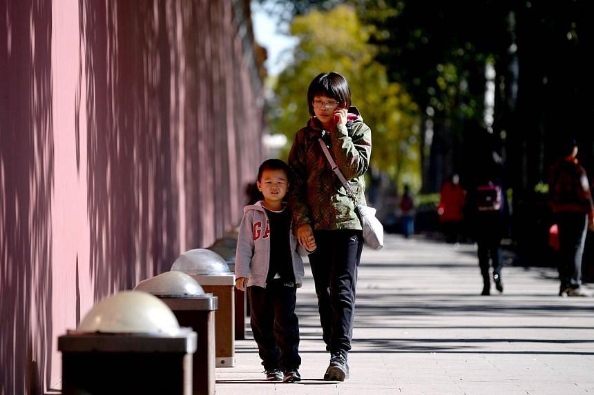 A woman and a child walk along a road in Beijing on Oct 31, 2015.