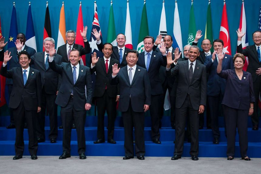 World leaders and delegates wave as they pose for a family photograph at the Group of 20 (G-20) summit in Brisbane, Australia.