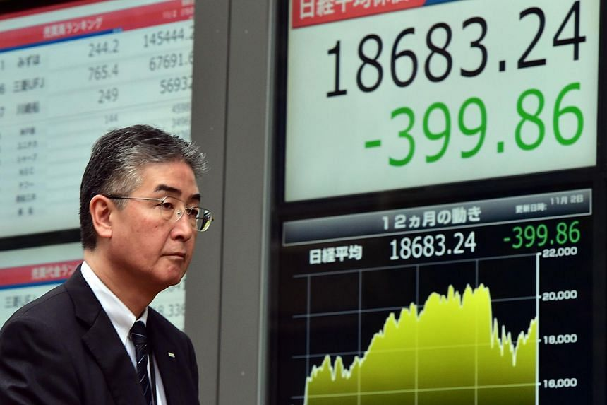 A man walking past a share prices board in Tokyo on Nov 2, 2015.