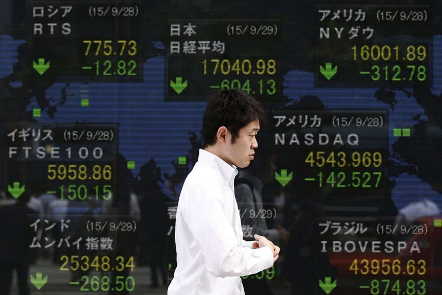 A passerby walks past an electric screen displaying stock market indices of various countries outside at a brokerage in Tokyo.