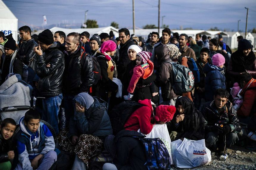 Migrants and refugees wait to enter a registration camp after crossing the Greek-Macedonian border near Gevgelija.