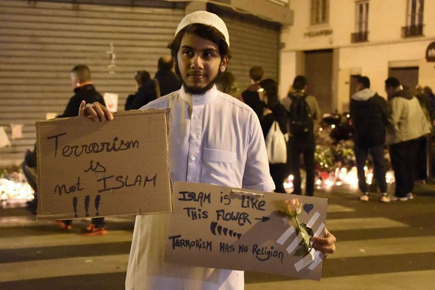 """A person holds placard reading """"Terrorism is not Islam. Islam is like this flower. Terrorsim has no religion"""" during a gathering at """"Le Carillon"""" restaurant one of the site of the attacks in Paris."""