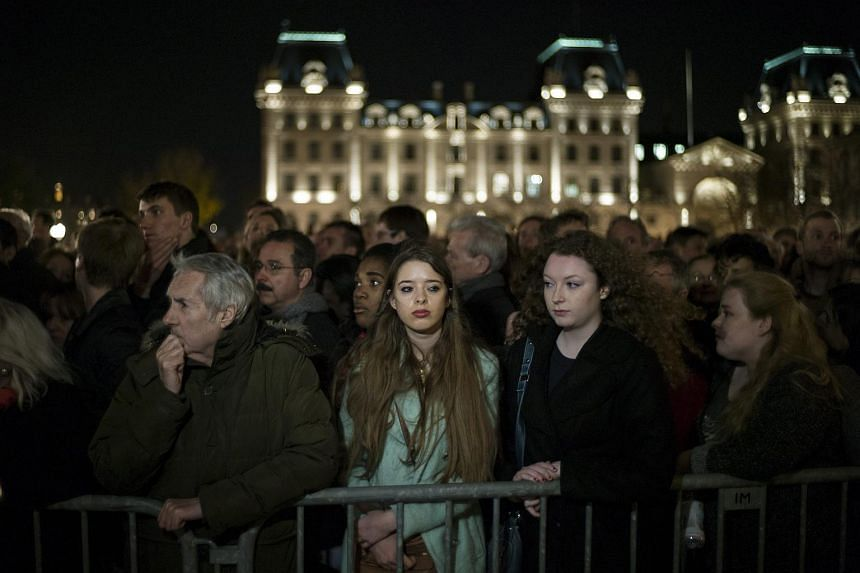 Thousands of people gather outside the Notre Dame Cathedral during a mass in Paris, France.