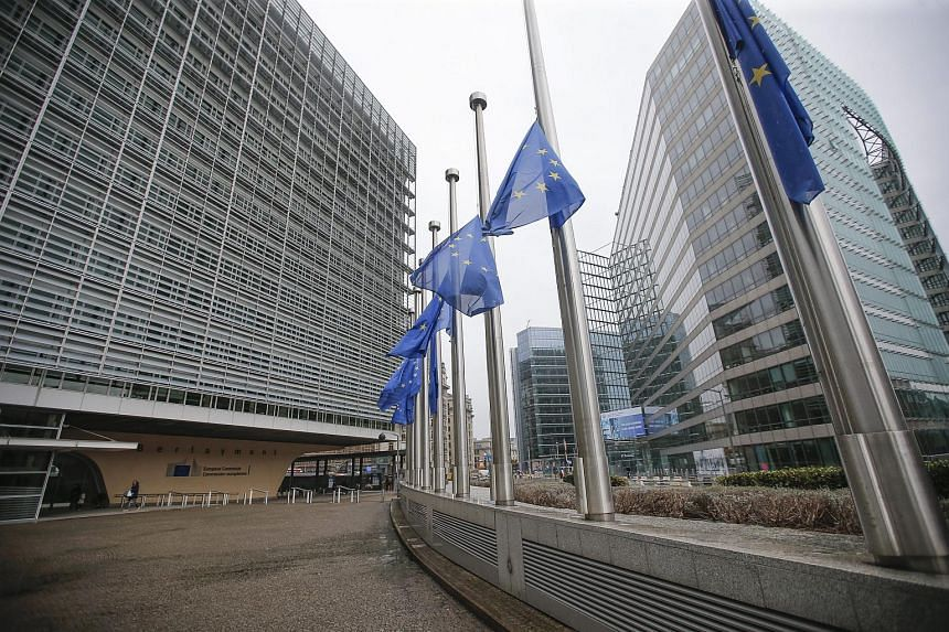 European Union flags are set at half mast in front of the European Commission headquarters in Brussels.