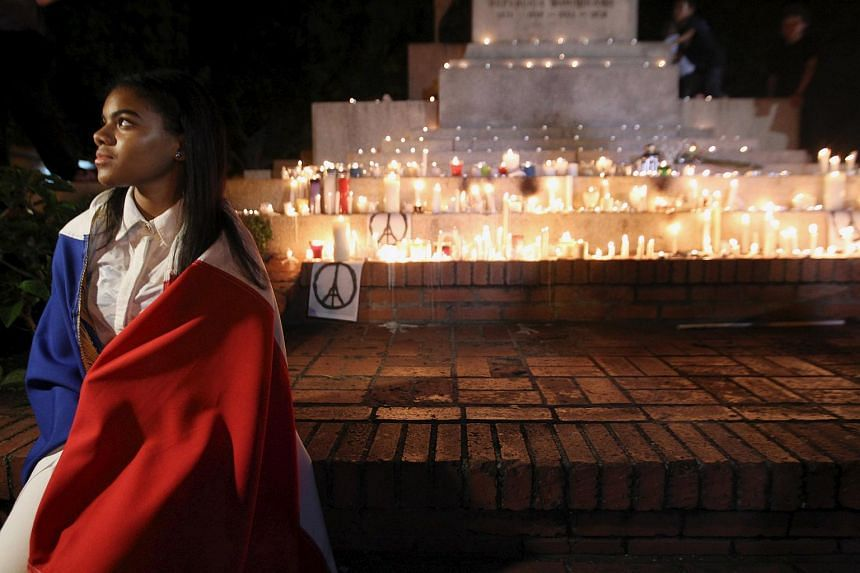 A woman with a French flag stands next to candles lit in tribute to the victims of the Paris attacks.