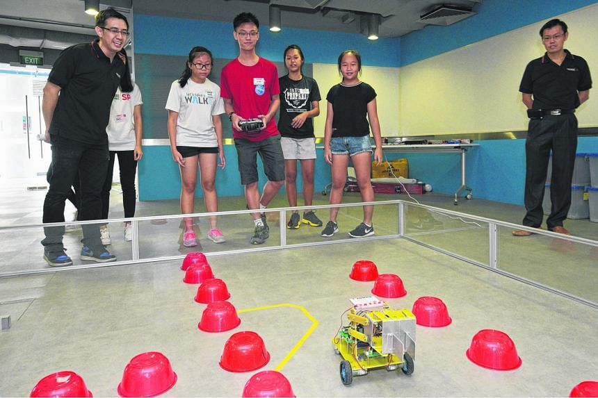 Mr Leong Ying Wei, lecturer at Singapore Polytechnic's School of Mechanical and Aeronautical Engineering, watching visiting secondary school students control a Robocar. The students were attending an engineering camp at the polytechnic last Saturday. The