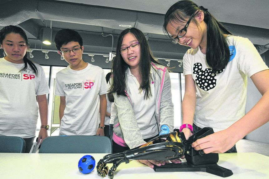Secondary school students getting hands-on experience with a robot during a one-day programme jointly organised by Singapore Polytechnic's School of Mechanical and Aeronautical Engineering, and School of Electrical and Electronic Engineering.
