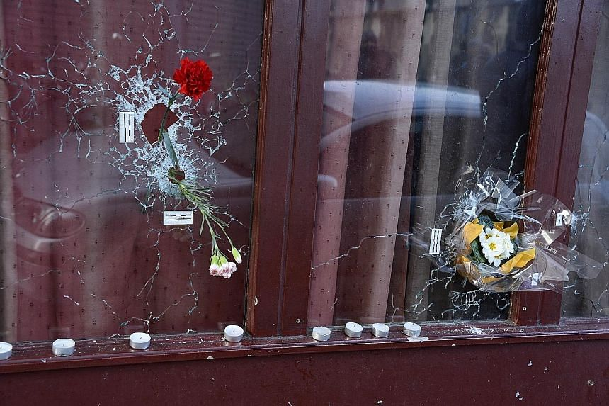Flowers placed in bullet holes at Le Carillon bar in Paris' 10th district yesterday, in memory of those who died in last Friday's attacks. The city was quiet yesterday, on the first of three days of national mourning. Police officers at the Place de