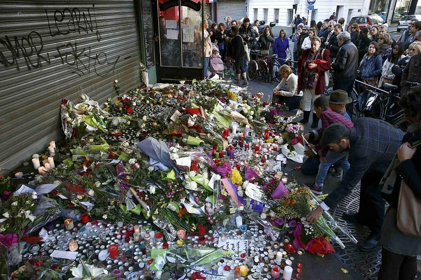 People paying their respects at one of the attack sites in Paris yesterday. The violence claimed 129 lives and injured 352, including 99 in a serious condition.
