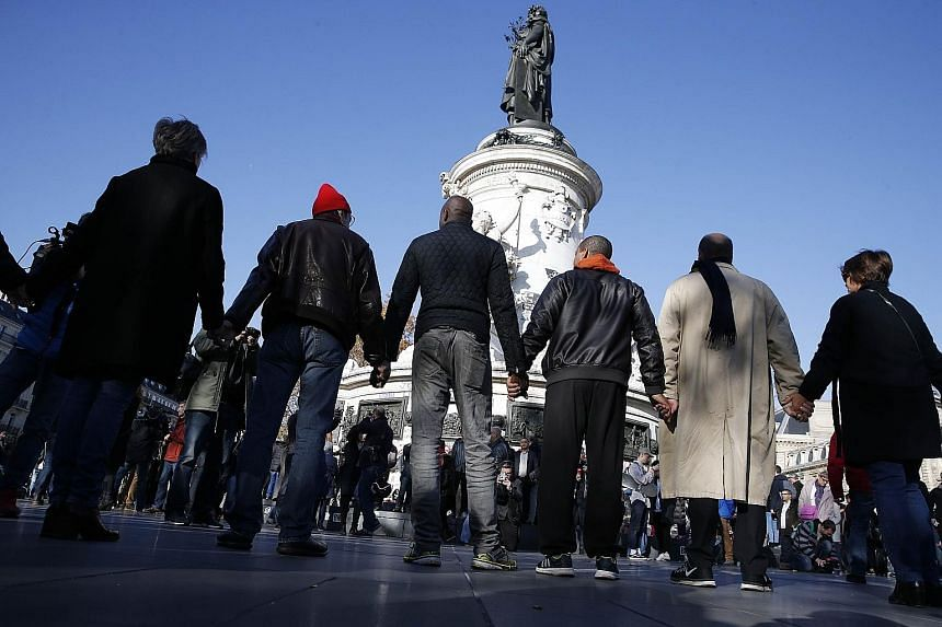 People joining hands around the Monument a la Republique yesterday. The Paris attacks have revived the spectre of terror acts with a relatively large number of perpetrators.