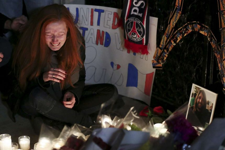 Polina Buckley, a friend of Eagles Of Death Metal's merchandise manager Nick Alexander (in photograph), cries as she sits near a makeshift memorial outside the Consulate of France in New York on Nov 14, 2015