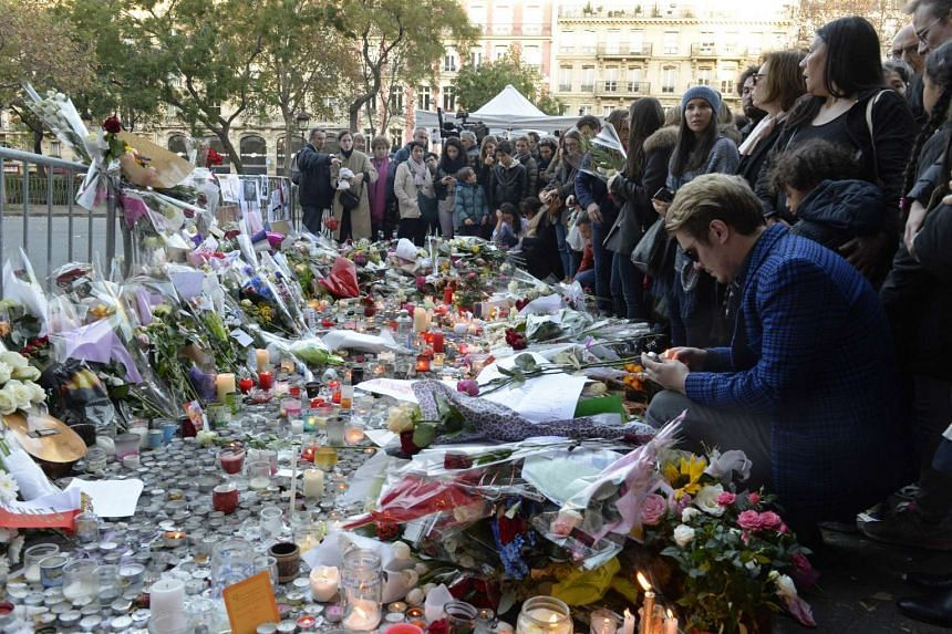 People mourning as they gather at a makeshift memorial near the Bataclan concert hall in Paris on Nov 15, 2015.