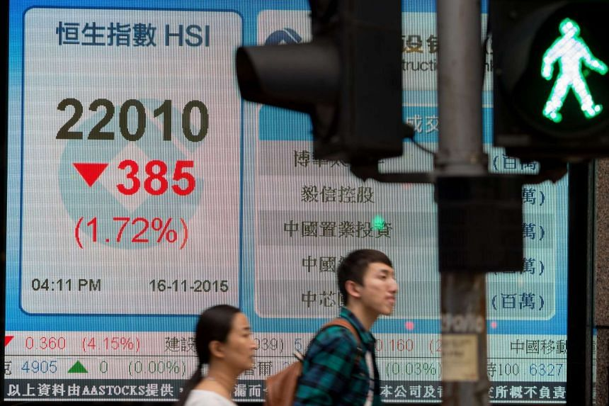 Pedestrians walk past a electronic board displaying the closing Hang Seng Index figure in Hong Kong on Nov 16, 2015.