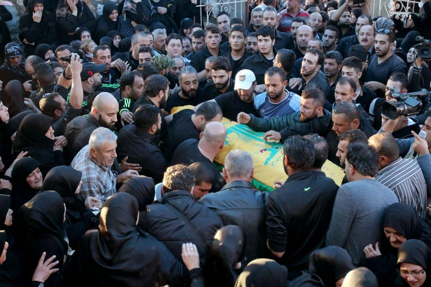 Lebanese mourners carry the coffin of Adel Tormos, who died trying to stop the bomber from entering the Shiites mosque full of worshippers on Nov 12.