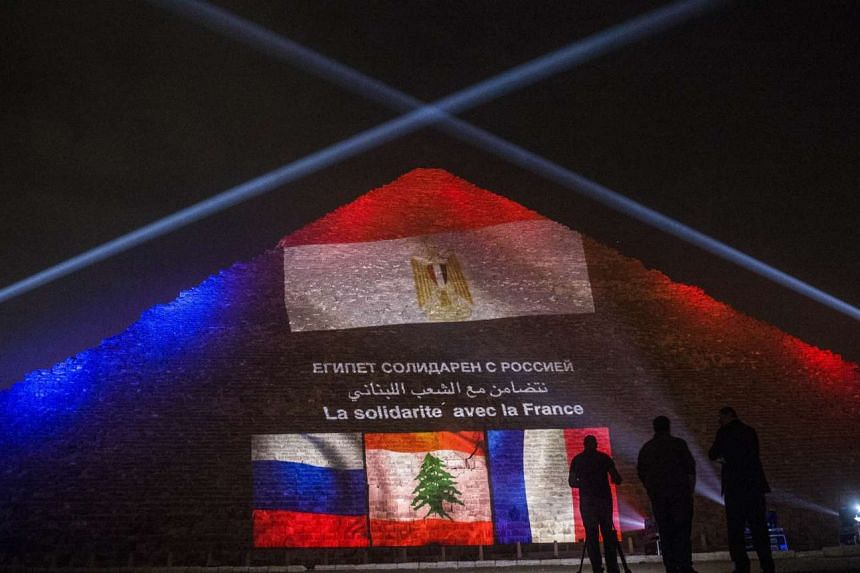The great pyramid of Khufu illuminated with the French, Lebanese and Russian flags in Giza, near Cairo, on Sunday.