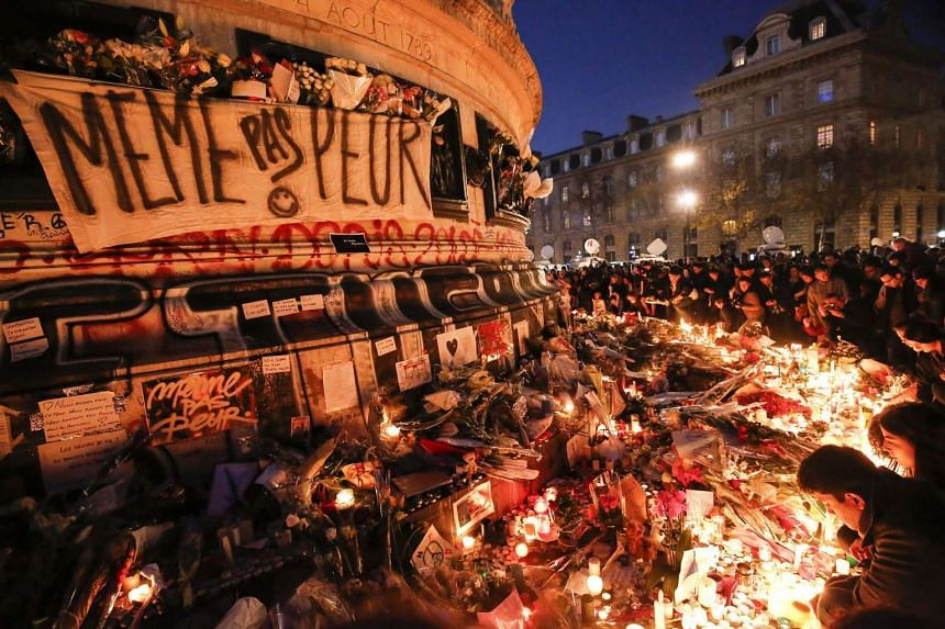 People leaving flowers, candles and messages at a memorial site at the Place de la Republique square on Sunday night.