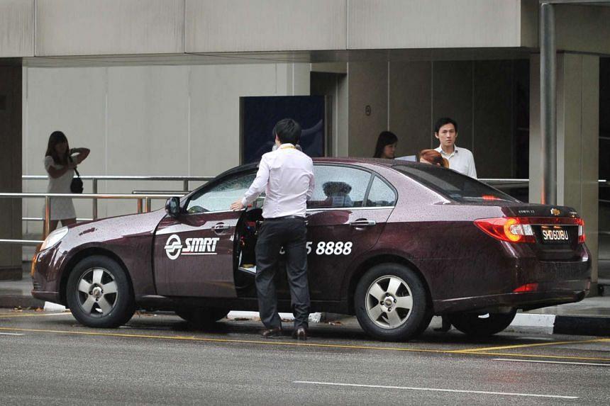 A passenger boarding an SMRT taxi.