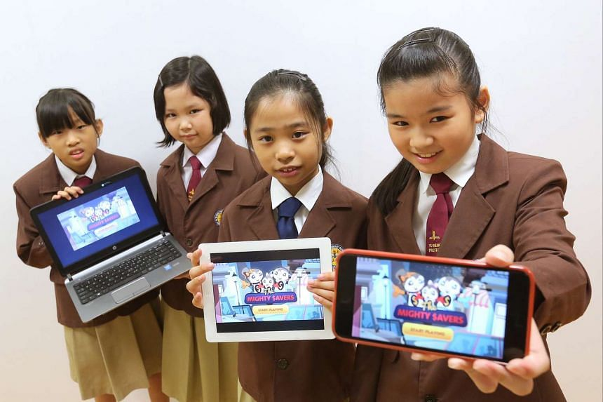 (From left) Seng Hui Ting, Cheryl Ho, Charmaine Thoi, and Toh Yi Xuan with the Mighty Savers game they helped to create.