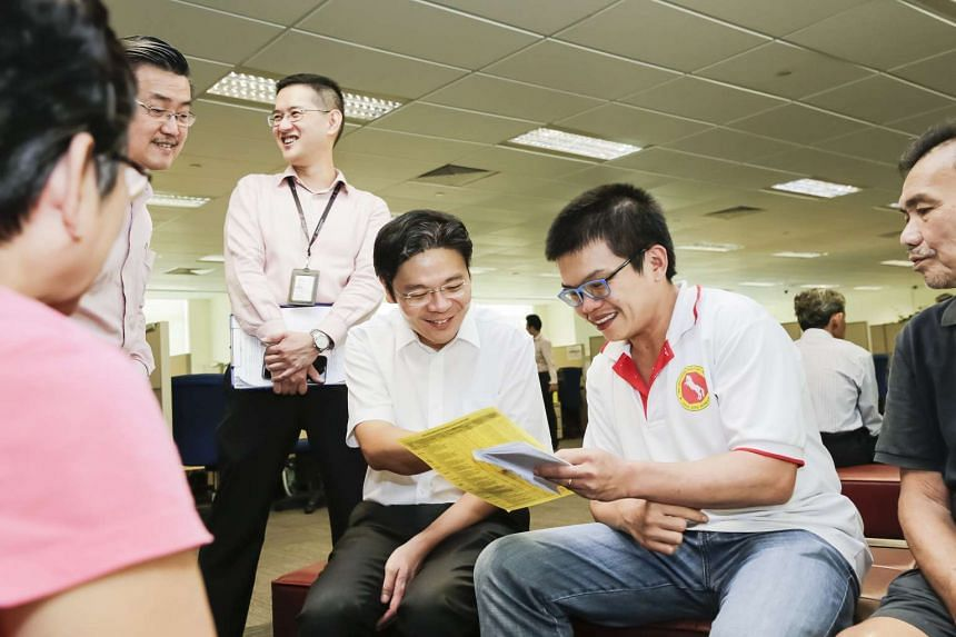 National Development Minister Lawrence Wong (centre) checking out the first day of the November sales exercise and interacting with flat applicants at HDB Hub on Nov 17, 2015.