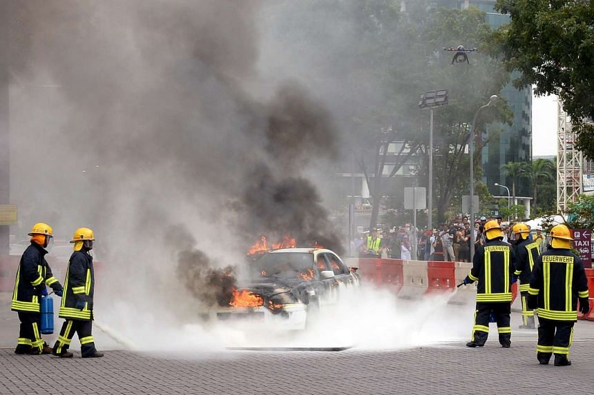 Officers extinguish the flames on the burning car during a simulated terrorist attack held as part of the 2014 Exercise Heartbeat.