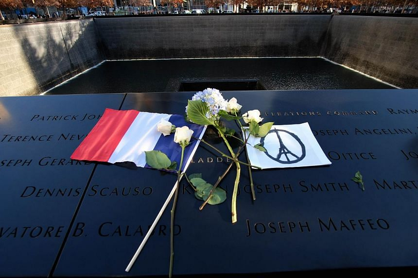 "A French flag, flowers and a ""Peace for Paris"" drawing are seen at the 9/11 memorial in New York during a vigil for the victims of the Paris terrorist attacks."