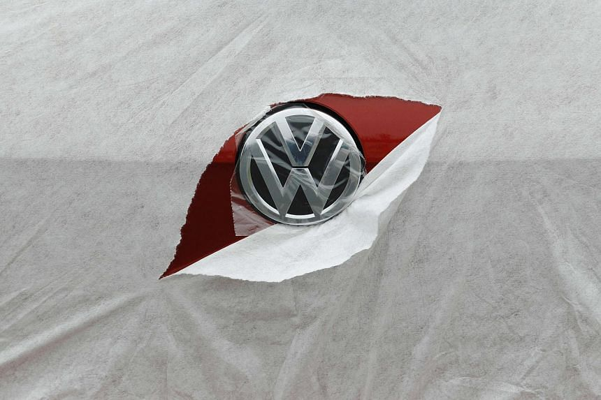 A Volkswagen logo is seen through torn car wrapping at a dealership in Portslade, southern England, in 2013.