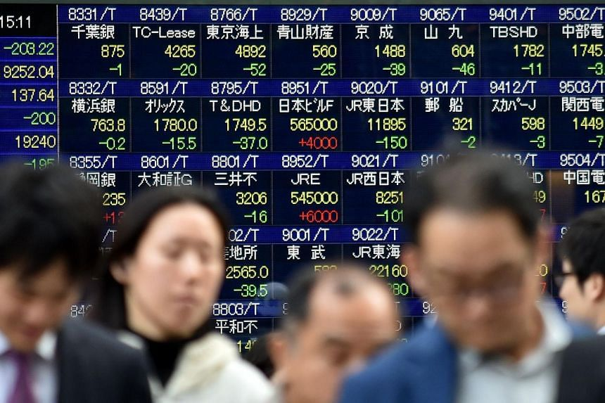 Pedestrians walking past a share prices board at the Tokyo Stock Exchange on Nov 16.