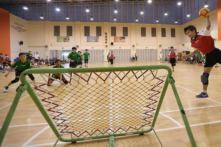 Greendale Primary's tchoukball captain Xavier Kew (extreme right), 11, about to score against St Anthony's Primary during the boys' final of the SPH Foundation National Primary Schools Tchoukball Championships held at Junyuan Primary School yesterday