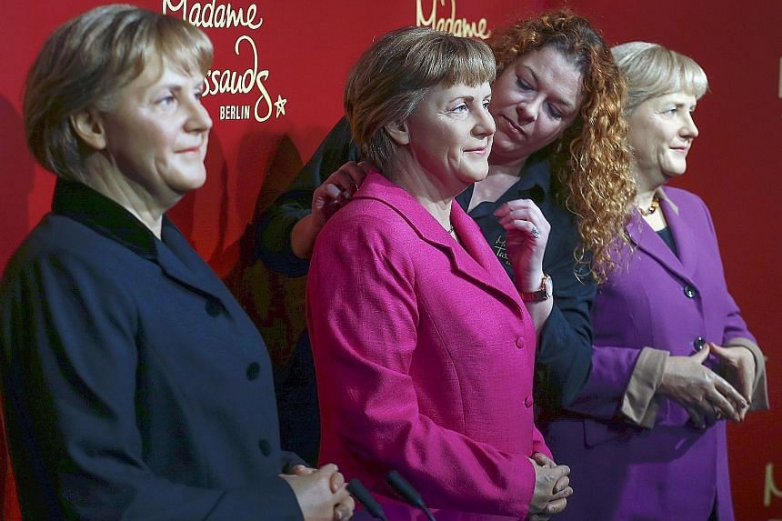 A staff member putting the finishing touches to wax figures of German Chancellor Angela Merkel at the Madame Tussauds wax museum in Berlin, Germany, yesterday. The museum is displaying three wax figures of Dr Merkel from her three legislative periods