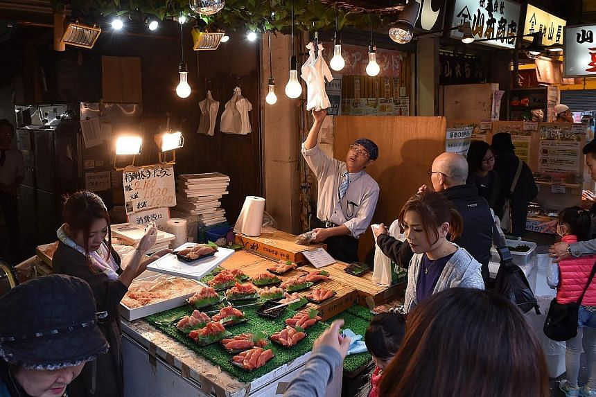 Customers at a seafood shop in Tokyo. Japan's Cabinet Office yesterday said GDP shrank 0.2 per cent in the July-September period, or an annualised contraction of 0.8 per cent, marking the second straight quarterly decline - considered a technical rec