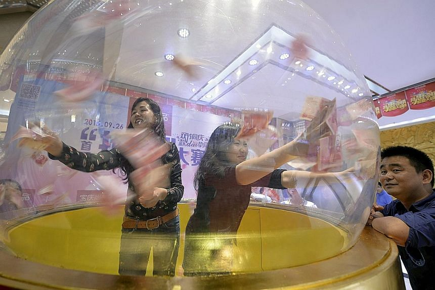Participants trying to catch 100-yuan notes flying inside a dome at a jewellery store's promotional event in Nanjing, Jiangsu province, on Sept 23. Since China surprised world markets by devaluing its currency around 2 per cent in August, net capital