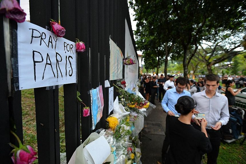 A queue formed outside the French Embassy, which held a memorial service yesterday for the victims of the Paris attacks. By 6.30pm, the line snaked out to Bukit Timah Road until Serene Centre.