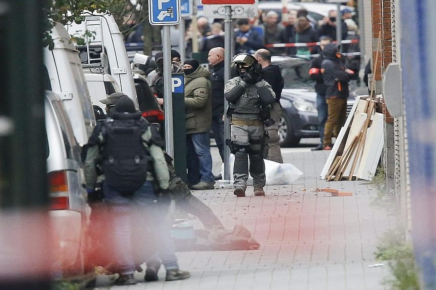 Police officers on a street in Molenbeek, Belgium, yesterday. Three brothers from the town are crucial suspects in Friday's attacks in Paris.