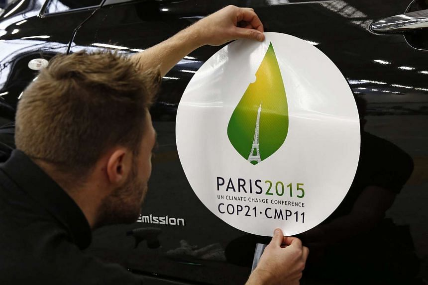 An employee installs a sticker with the logo of the COP21 Climate Change Conference on a Nissan LEAF electric car.