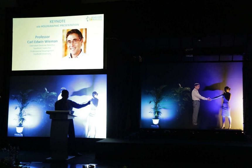 Professor Carl Edwin Wieman giving his presentation via an interactive 3D holographic display or hologram direct from Stanford University in the US.