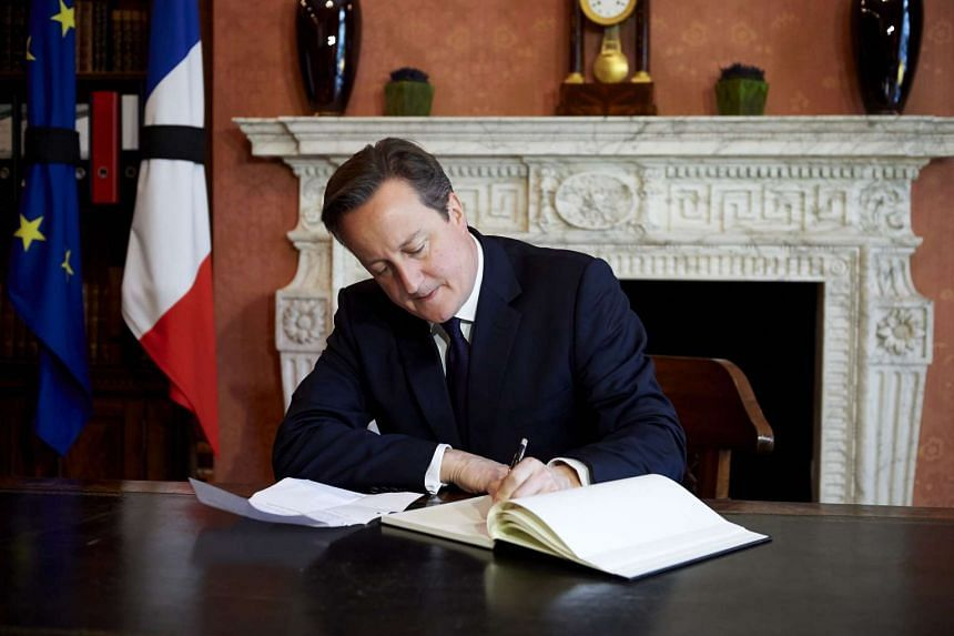 British Prime Minister David Cameron signing a book of condolences at the French Ambassador's residence in London on Nov 17, 2015.