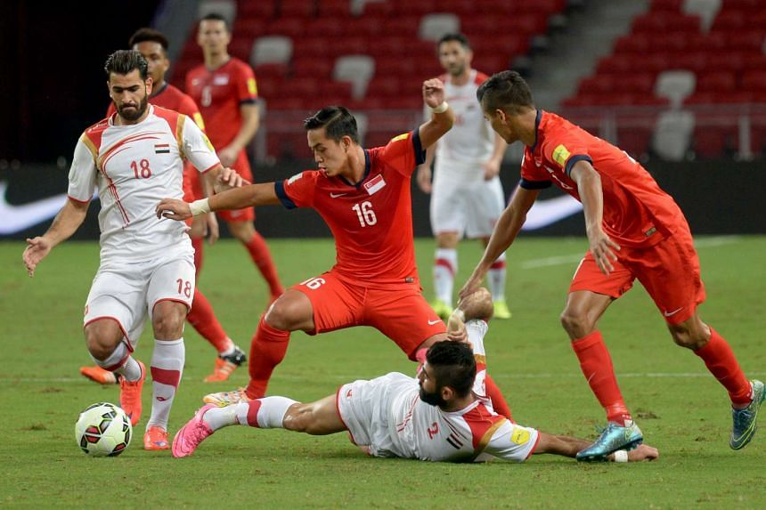 Singapore's Hafiz Sujad (centre) and Safuwan Baharudin trying to gain possession from Syria during their Fifa World Cup qualifying match at the National Stadium on Nov 17, 2015.
