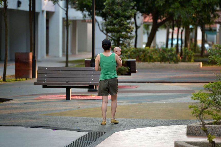 A woman carrying her baby in an open space along Jurong West St 52.