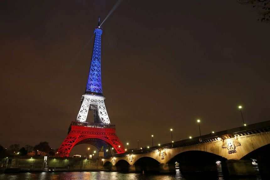 The Eiffel Tower is lit with the colours of the French flag on Monday.