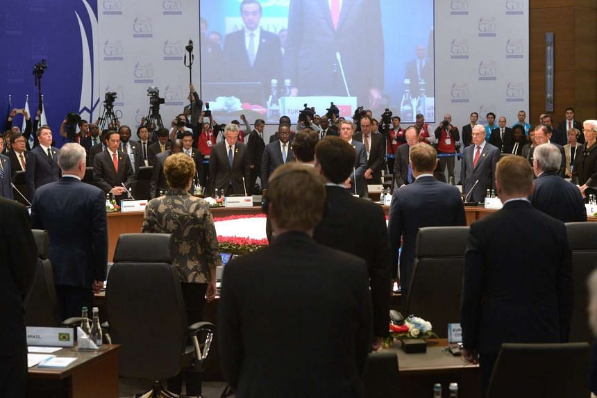 Leaders and delegates stand and observe one minute of silence for the victims of the Paris attacks at the working session for G20 leaders.