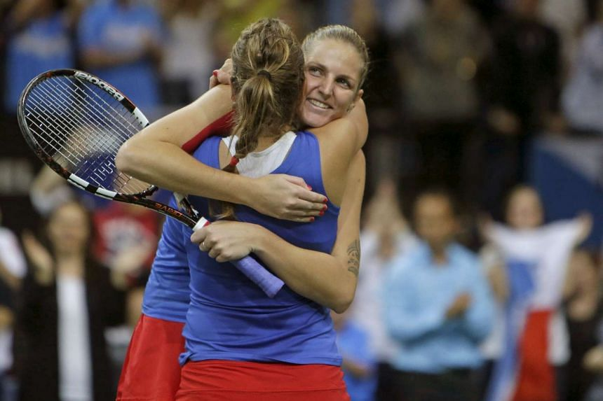 Czech Republic's Karolina Pliskova (right) and Barbora Strycova celebrating after winning against Russia's Anastasia Pavlyuchenkova and Elena Vesnina during their final match of the Fed Cup tennis tournament in Prague on Nov 15.