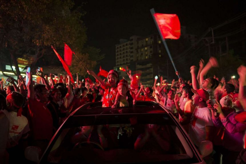 Supporters of Aung San Suu Kyi's National League for Democracy (NLD) party cheering outside the NLD headquarters in Yangon.